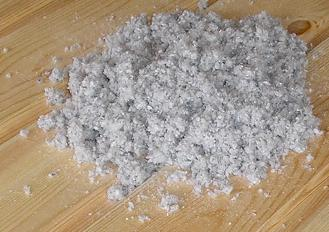 Photo of a pile of cellulose insulation on a wood floor.