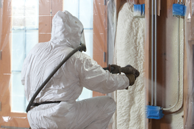 Photo of person spraying insulation.