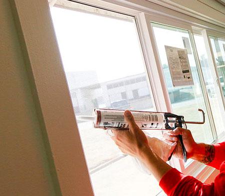 Photo of someone applying caulk to a window.